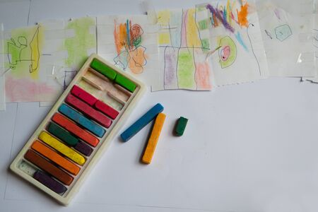 Drawing on the imagination of children with chalk colors in various colors on white background paper.