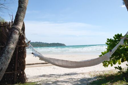 A white hammock with a rope tied to a coconut tree for relaxing on the beach. Banco de Imagens
