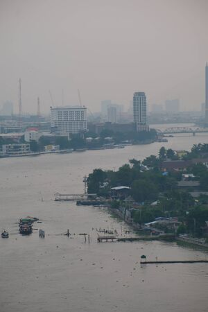 Views from the window of Chao Phraya River in big cities like Bangkok on a foggy day.