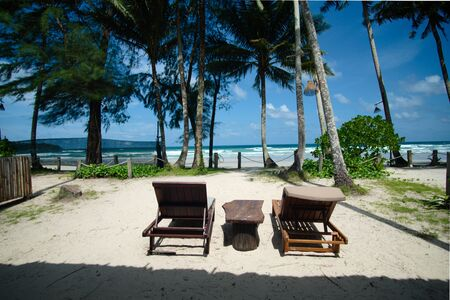 Relaxing chair for hotel guests placed facing the sea at a beautiful beach. Banco de Imagens
