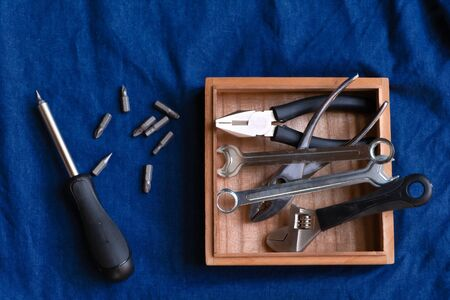 Hand tools such as pliers, wrenches, screwdrivers, many types of screwdrivers and other tools that are in a wooden box placed on a blue denim background. Banco de Imagens