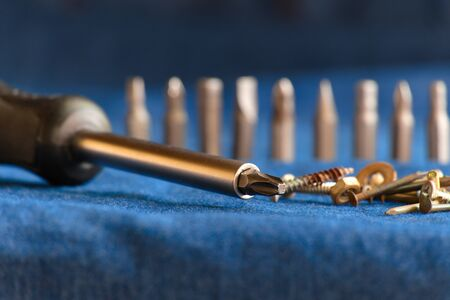 Close-up of a stainless screwdriver. Various screwdriver heads, including screws, nuts and nails placed on a blue denim background Banco de Imagens