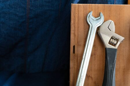 Hand tools include Wrench and plier leaning on a wooden box on a blue denim background.