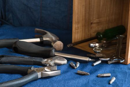 Hand tools such as hammers, pliers, wrenches, screwdrivers, many types of screwdrivers and other tools that are in a wooden box placed on a blue denim background.