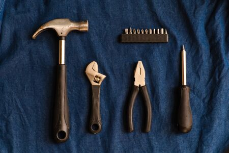 Hand tools such as hammers, pliers, wrench and screwdrivers are arranged on a blue denim background. Banco de Imagens