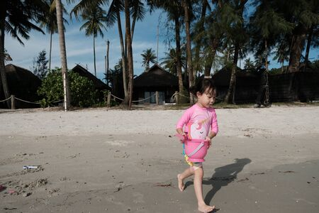 An Asian girl wearing a pink swimsuit is running with a sand bucket at a beautiful beach. Banco de Imagens