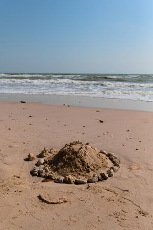 A sand castle surrounded by rocks is bounded by children at a beautiful beach.