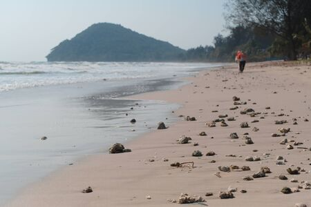 A beach in Thailand Which is lined with rocks on a day with very strong wind and waves washed ashore all the time.