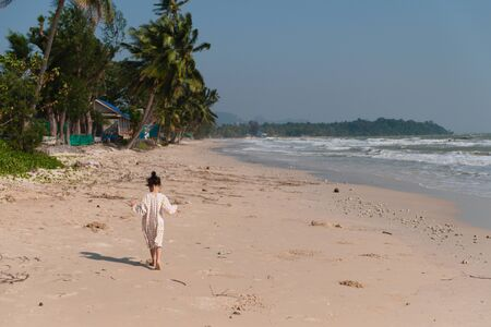 An Asian girl in a white-yellow pajamas walking on a beach on a day with monsoon and strong waves all day.