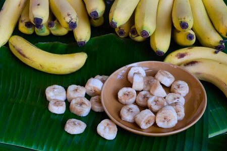 Fresh bananas are peeled and cut into pieces, put on a brown dish, placed on a green banana leaf Banco de Imagens