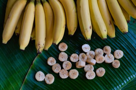 Fresh bananas are peeled and cut into pieces, put on a green banana leaf background.