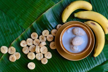 Traditional Thai dessert: Fresh bananas are peeled and cut into pieces and placed on a brown plate. And Thai desserts made from bananas and coconut milk placed on a green banana leaf background,