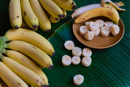 Fresh bananas are peeled and cut into pieces, put on a brown dish, placed on a green banana leaf background.