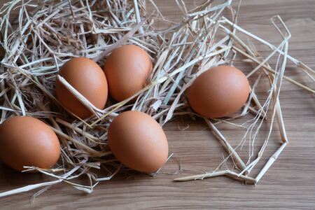The eggs in a straw were laid on a wooden table.
