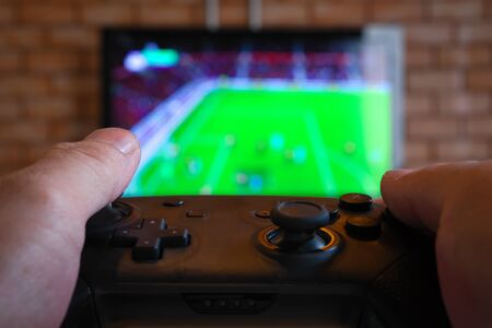 Gamer control the joy while playing football video games. Banco de Imagens