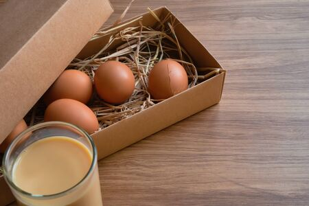 Eggs on straw in a brown box and a glass of milk placed on a wooden table.