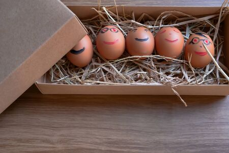 Several eggs that were written as smiling faces were placed in a brown box on a wooden table. Banco de Imagens