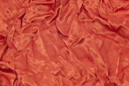 A luxurious red satin folded fabric, useful for backgrounds photo