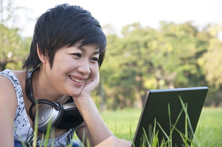 Asian lady using computer in a field photo