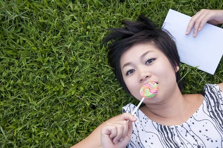 Young woman eating a candy in the park photo