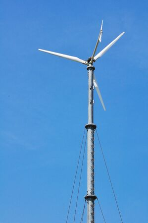 Wind turbine generating electricity on blue sky photo