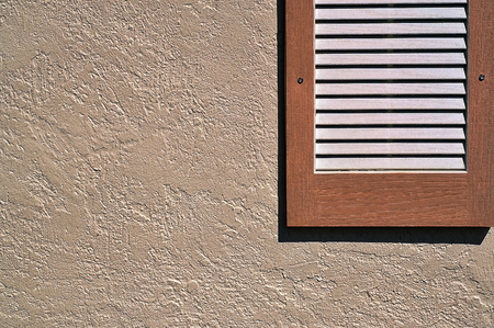 apartment living: Shutter on exterior stucco wall Stock Photo