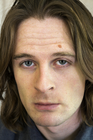 brown hair blue eyes: Young adult male with long hair Stock Photo
