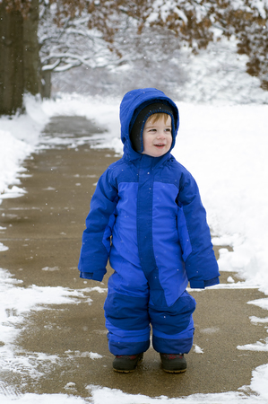 flurry: A caucasian toddler in a blue snowsuit stands on a sidewalk in winter while flurries fall