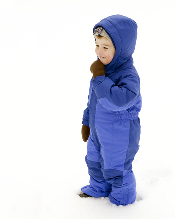 A young boy plays outside in the snow wearing a blue snowsuit Stock Photo