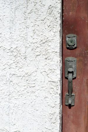 uncluttered: Architectural detail shot of an old door handle on a rust colored door and a white exterior stucco wall Stock Photo