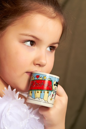The little girl in a white dress drinks from a small cup. Stock Photo - 8879176