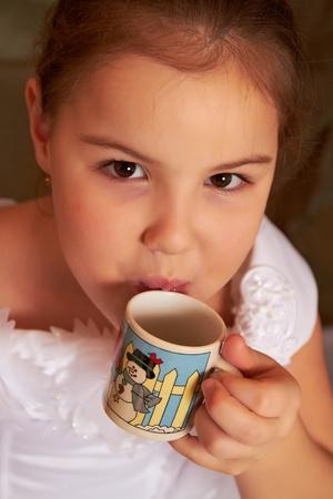 Das kleine M�dchen in einem wei�en Kleid Getr�nke aus einer kleinen Tasse.