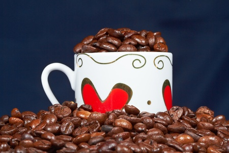 White cup with hearts stands sprinkle on the table beans roasted coffee.