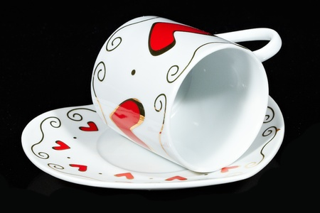 White cup with hearts isolated on black background. Stock Photo