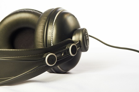 Professional black headphones, lying on a white table.