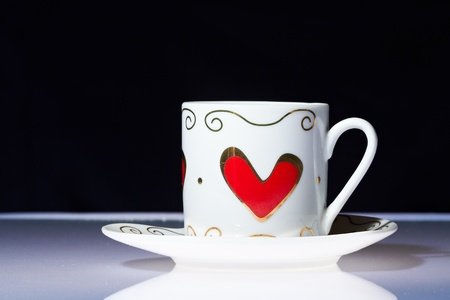 White cup with hearts stands on a white table with a dark background. Stock Photo