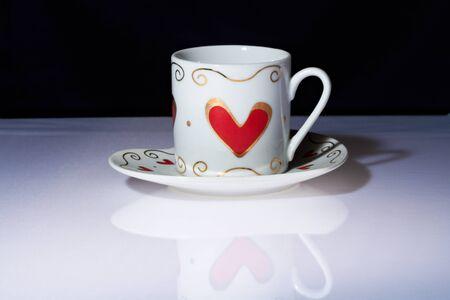 White Cup with Hearts steht auf einem wei�en Tisch mit einem dunklen Hintergrund.
