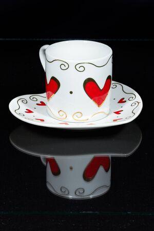 White Cup with Hearts ist ein schwarz Tisch, spiegelt sich in es.