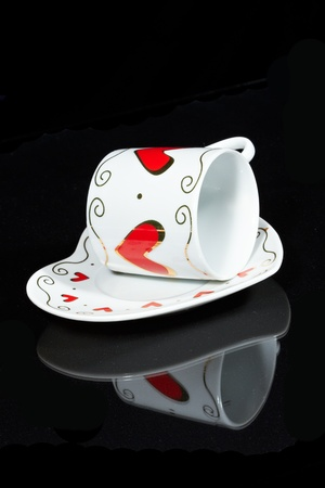 White cup with hearts is a black table, reflected in it.