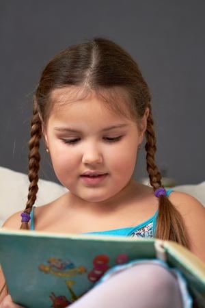 Ein kleines M�dchen sitzt und liest.