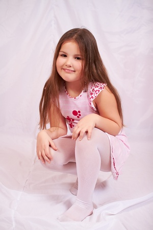 Little girl sitting on her haunches. Stock Photo - 8970044