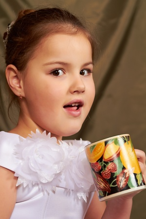 The little girl in a white dress drinks from a large mug.