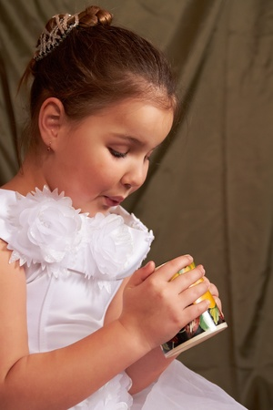 Das kleine M�dchen in einem wei�en Kleid trinkt aus einer gro�en Tasse.