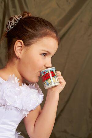 Das kleine M�dchen in einem wei�en Kleid trinkt aus einer kleinen Tasse. Lizenzfreie Bilder