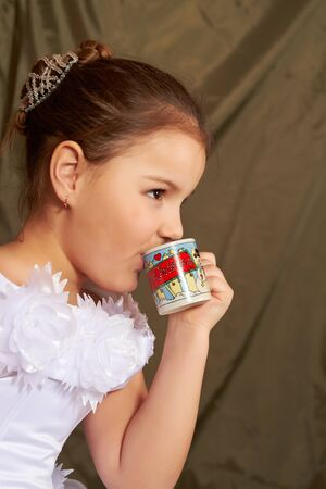 The little girl in a white dress drinks from a small cup. Stock Photo