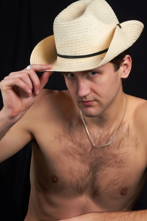 A man sitting in a hat, bare-chested, looks sexy and attractive  photo