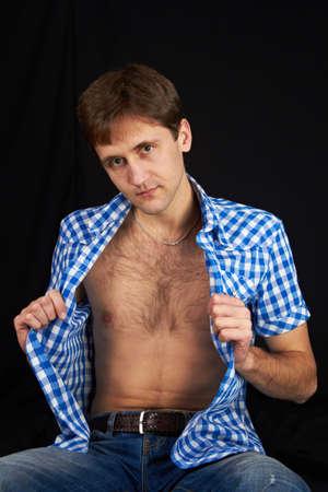 Ein Mann sitzt, zeigt ihre sexy Br�ste