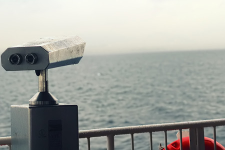 there is a binocular at ship with horizon and sea photo