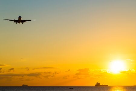airplane landing: An airplane approaching the runway for landing during the sunset