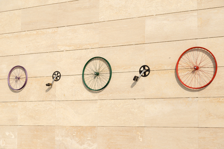 red metal background: Wheel rim parts of bicycle on the wall Stock Photo